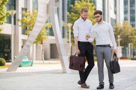 Business colleagues in summer walking and  talking in city