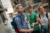 Tourist group of  friends discovering city on foot and travelling