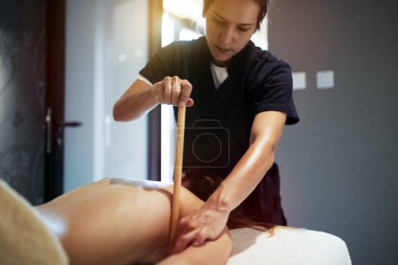 Masseur giving massage therapy to masseuse at wellness resort