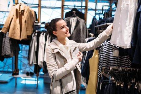 Photo pour Jeune femme attrayante acheter des vêtements dans le centre commercial - image libre de droit