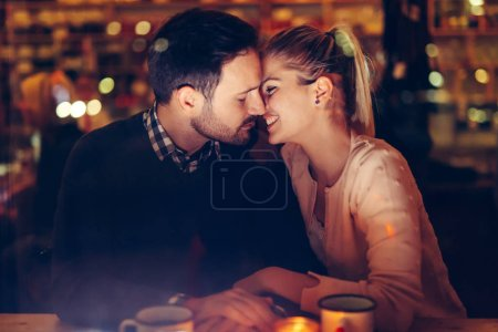 Photo for Romantic young couple dating in pub at night - Royalty Free Image
