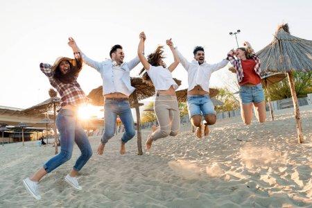 Photo pour Groupe de joyeux amis faire la fête sur la plage et s'amuser - image libre de droit