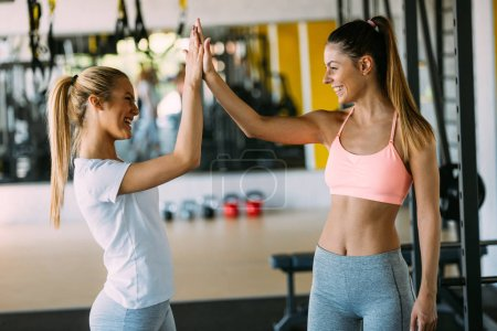 fitness, sport, friendship and lifestyle concept - beautiful women making high five gesture in gym