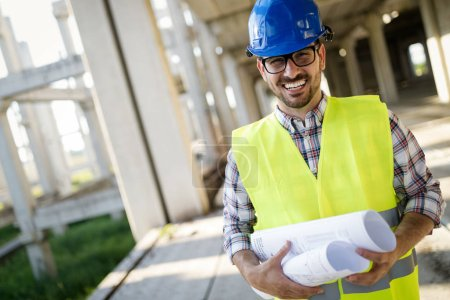 Confident architect holding rolled up blueprints at construction site
