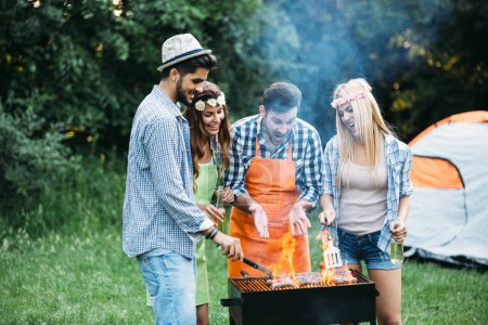 Photo for Cheerful friends spending time in nature and having barbecue - Royalty Free Image