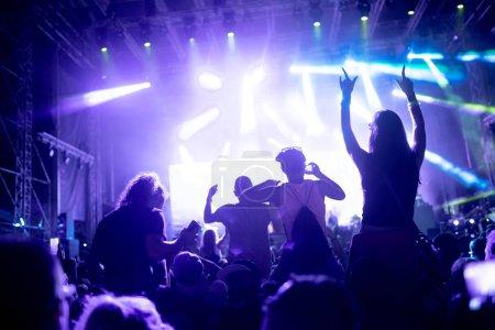 Portrait of happy dancing crowd enjoying at music festival