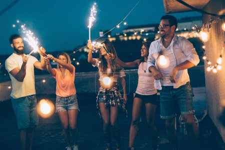 Group of friends enjoying rooftop party with sparklers