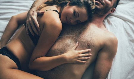 Attractive happy couple resting together after sex in bedroom