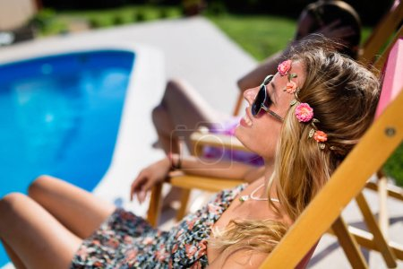 Photo for Beautiful women relaxing and sunbathing in resort - Royalty Free Image