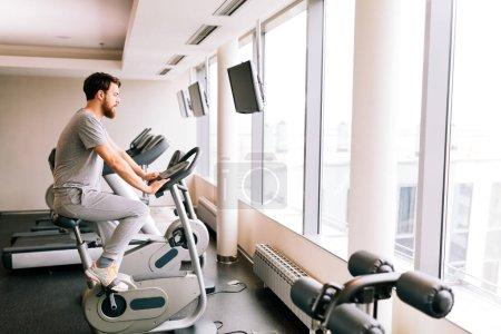 Photo pour Entraînement cardio homme sur un vélo dans une salle de sport - image libre de droit