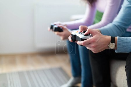 Photo for Young couple having fun playing video games at home - Royalty Free Image