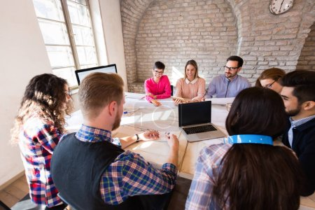 Photo for Picture of young attractive architects discussing in office - Royalty Free Image