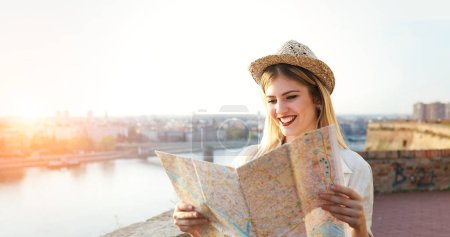 Photo for Tourist woman holding travelers map to travel to destination - Royalty Free Image