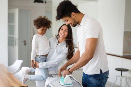Photo pour Jeune couple heureux à la maison faisant corvées hosehold et repassage - image libre de droit