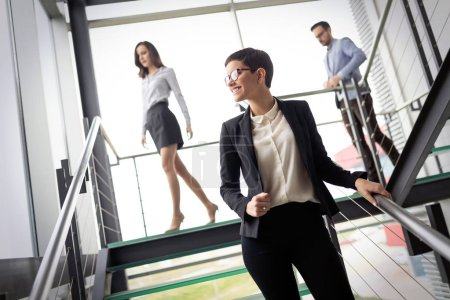 Photo for Confident young business partners walking down in office building and talking - Royalty Free Image