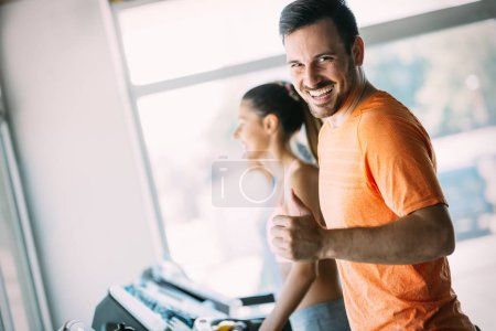 Photo for Young handsome man doing cardio training on treadmill in gym - Royalty Free Image