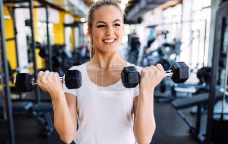Photo pour Gros plan image du sourire jolie femme fit dans la salle de gym - image libre de droit