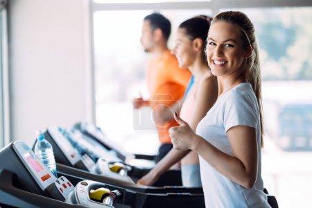Photo pour Fitness, sport, concept de mode de vie sain et qui exerce - groupe de gens heureux en gym - image libre de droit