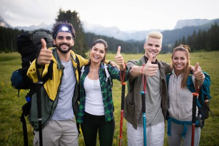 Photo for Hiking with friends is so fun. Group of young people with backpacks walking together and looking happy - Royalty Free Image