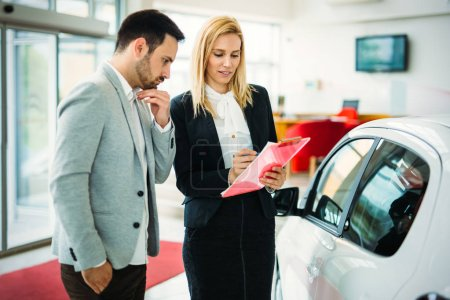 Photo for Young beautiful female car sales consultant working in showroom - Royalty Free Image