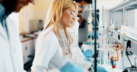 Photo pour Étudiante séduisante en chimie travaillant en laboratoire - image libre de droit