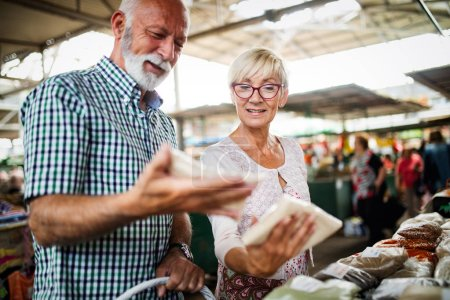Photo for Shopping, food, sale, consumerism and people concept - happy senior couple buying fresh food on the market - Royalty Free Image