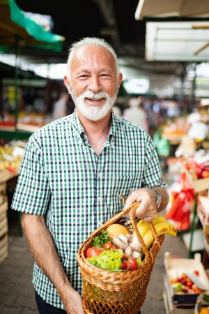 Photo for Handsome senior man shopping for fresh vegetable and fruit in a market - Royalty Free Image