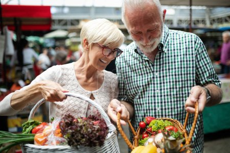 Photo for Only the best fruits and vegetables. Beautiful senior couple buying fresh food on the market - Royalty Free Image