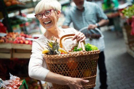 Photo for Picture of senior happy woman at marketplace buying vegetables - Royalty Free Image