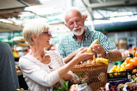 Foto de Senior pareja elegir bio alimentos frutas y verduras en el mercado durante compras semanales - Imagen libre de derechos