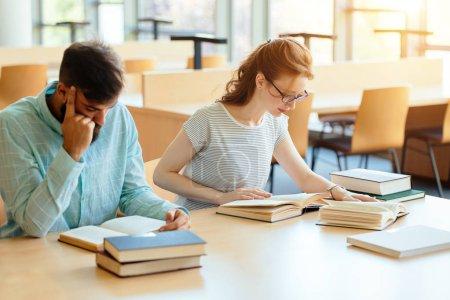Photo pour Jeunes étudiants étudiant à la bibliothèque pour l'examen - image libre de droit