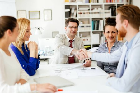 Photo for Busy young businesspeople shakind hands in office - Royalty Free Image