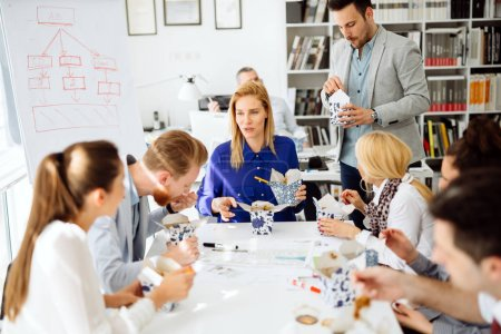 Photo for Business people eating meals in office - Royalty Free Image