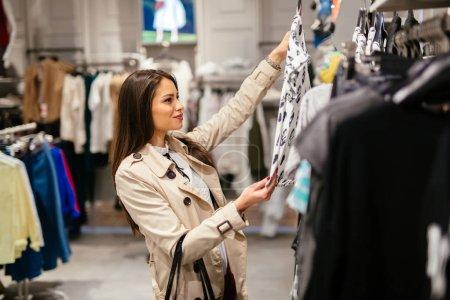 Photo pour Belle jeune et heureuse femme d'affaires acheter des vêtements - image libre de droit