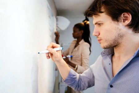Photo for Smart people writing on whiteboard in search of a solution - Royalty Free Image