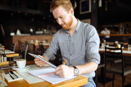 Businessman taking notes in cafe and writing down ideas