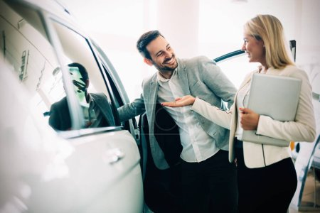 Photo for Professional salesperson selling cars at dealership to new buyer - Royalty Free Image