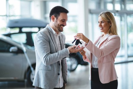 Photo for Salesperson during work with customer at car dealership. Giving keys to new car owner. - Royalty Free Image