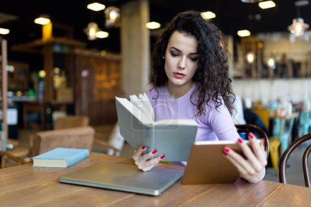 Photo for Young woman reading book and holding tablet in coffee shop - Royalty Free Image