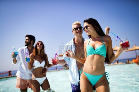 Photo for Summer party. Group of friends at beach drinking coctails and having fun - Royalty Free Image