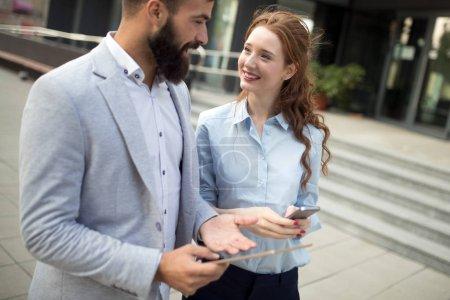 Photo pour Homme d'affaires souriant et femme bavardant dans la rue - image libre de droit