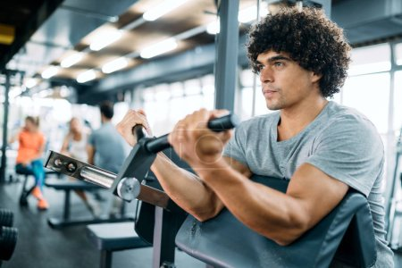 Photo for Determined male working out in gym lifting weights - Royalty Free Image