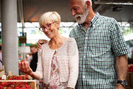 Photo pour Couple de personnes âgées achetant des légumes frais au marché local - image libre de droit