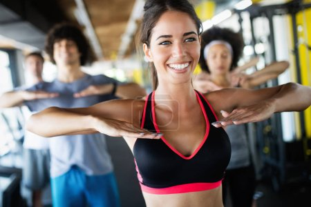 Photo for Group of young fit people doing exercises in gym - Royalty Free Image