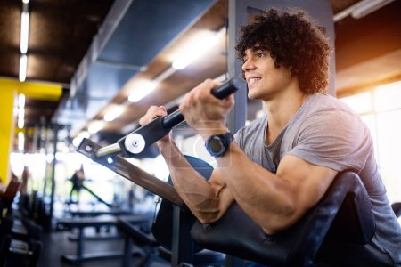 Photo for Young handsome man doing exercises in gym - Royalty Free Image