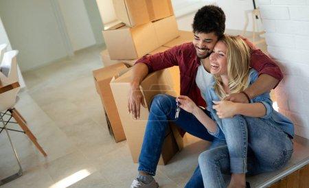 Photo pour Couple profitant de leur nouvelle maison luxueuse et étreindre dans le salon - image libre de droit