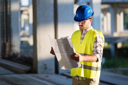 Photo pour Ingénieurs travaillant sur un chantier de construction tenant un tirage de bleus - image libre de droit