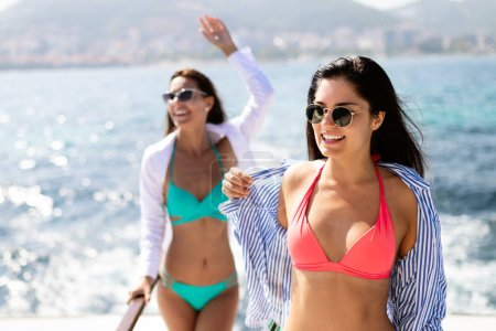 Photo for Happy women friends on vacation having fun on beach in summer - Royalty Free Image