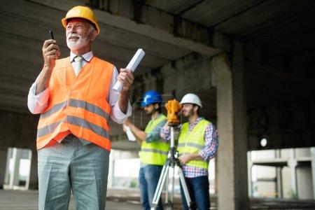Photo pour Ingénieur, contremaître et travailleur discutant et travaillant sur le chantier de construction - image libre de droit