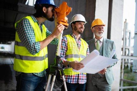 Photo pour Les ingénieurs en construction discutent avec les architectes sur le chantier ou sur le chantier - image libre de droit